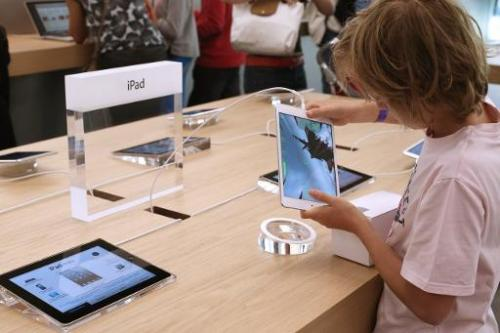 A child plays with an Apple iPad Mini at an Apple store in Paris on July 6, 2013