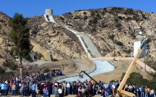 A crowd gathers to watch a re-enactment of the moment the Los Angeles Aqueduct gates were first opened 100 years ago, on Novembe