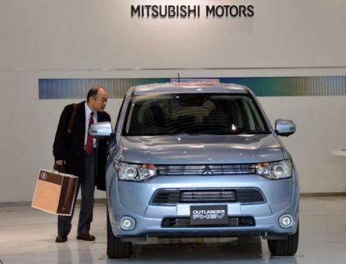 A customer looks at Mitsubishi Motors' new plug-in hybrid SUV in Tokyo on February 5, 2013
