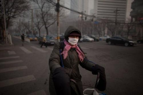A cyclist wearing a mask crosses a road in severe pollution in Beijing on January 12, 2013