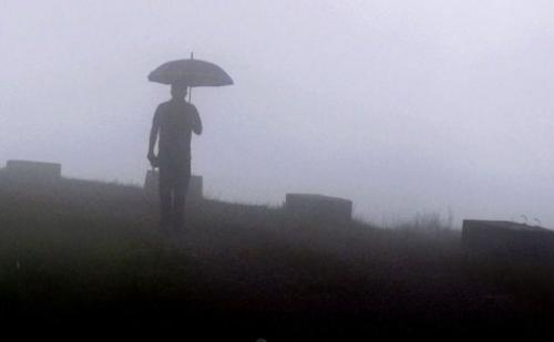 A pedestrian walks through fog in Mawsynram village in the northeast Indian state of Meghalaya, June 21, 2013