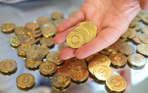 A software engineer holds physical Bitcoins, minted at his shop in Sandy, Utah, on April 26, 2013
