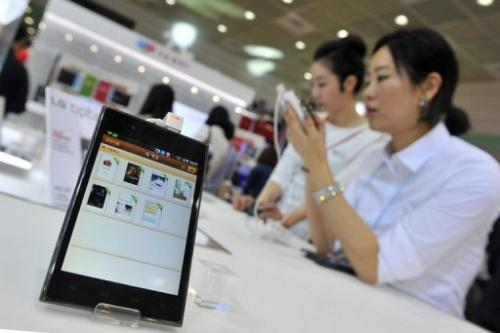 "A South Korean woman inspects LG's smartphone ""Optimus Vu"" during an IT show in Seoul on May 15, 2012"
