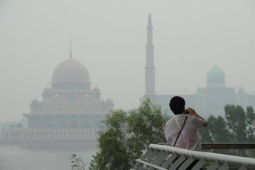 A visitor takes pictures as haze shrouds buildings in Putrajaya, outside Kuala Lumpur, on June 26, 2013