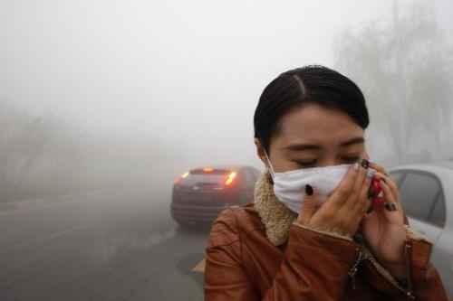 A woman wearing a mask covers her mouth with her hands as she walks in the smog in Harbin, China's Heilongjiang province, on Oct