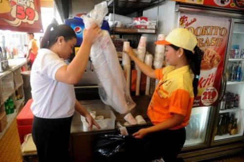 Employees of a fast food store put plastic cups into a trash bag, in Makati City, on June 20, 2013