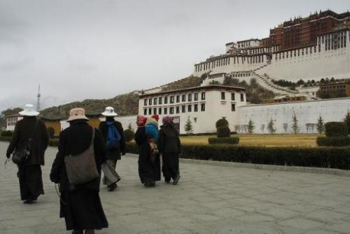 File photo of Tibetans passing the Potala Palace in the capital Lhasa, where pollution levels have reached new heights, shroudin