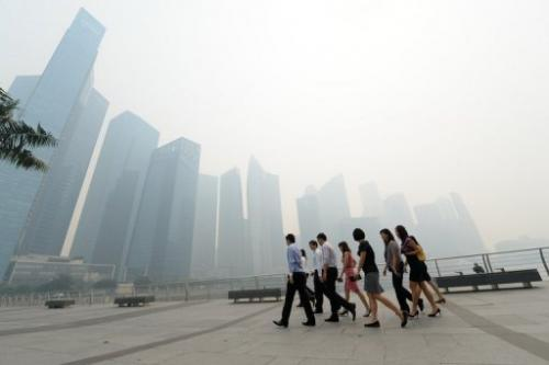 Office workers return from a lunch break in front of buildings blanketed by haze in Singapore on June 19, 2013
