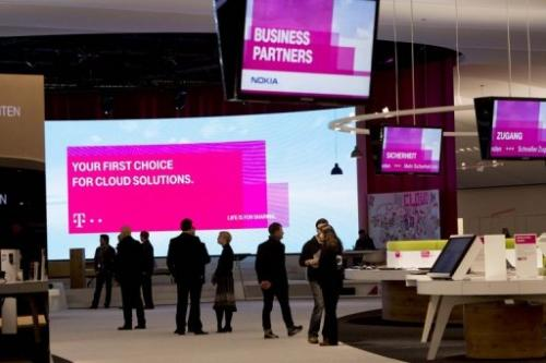 People are seen at the booth of Deutsche Telekom at the CeBIT high-tech fair, in Hanover, on March 4, 2013