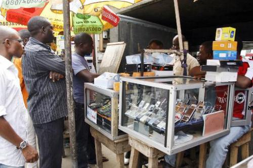People queue outside a mobile phone stand in Lagos, on August 18, 2008