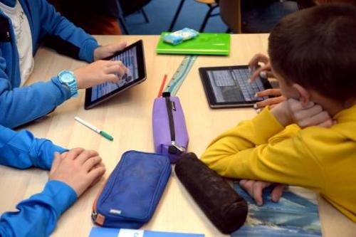 Pupils use tablets during courses in a classroom at a school in Saint-Brieuc, western France on September 12, 2013