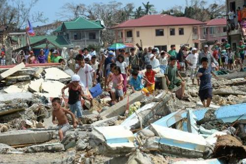 Residents walk through debris as they rush to a rescue helicopter delivering relief foods in Hernani town, Eastern Samar provinc