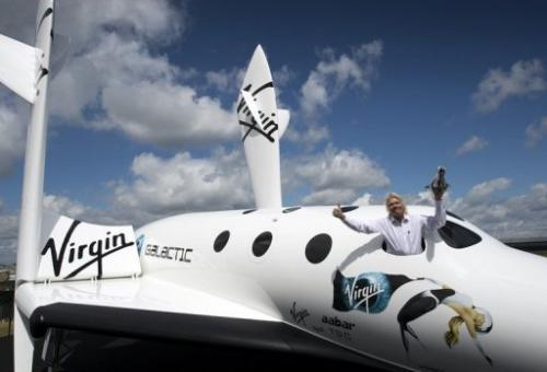 Richard Branson poses in the window of a replica of the Virgin Galactic spaceship in England on July 11, 2012