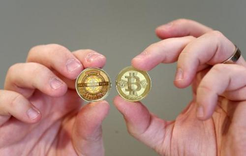 Software engineer Mike Caldwell shows the front (R) and back, hologram side, (L) of a physical Bitcoin he minted in his shop on
