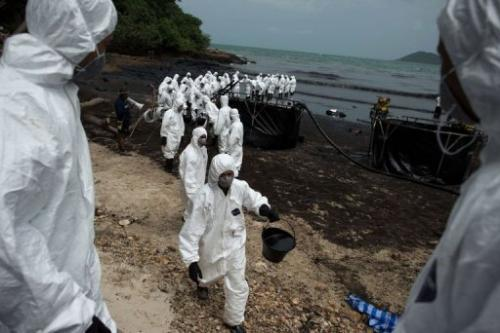 Thai Royal Navy personnel work to clean up oil from Ao Phrao beach on the island of Ko Samet on July 30, 2013
