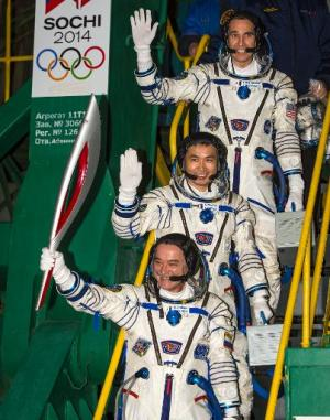This NASA photo shows Expedition 38 Soyuz Commander Mikhail Tyurin of Roscosmos, holding the Olympic torch, Flight Engineer Koic