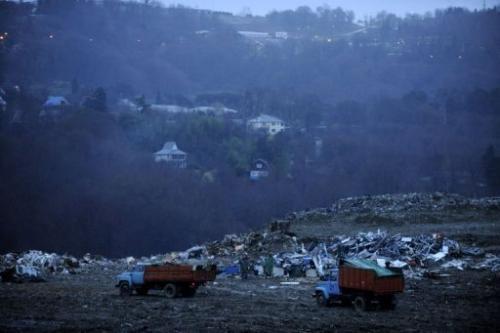 Trucks unload rubbish at a dumping ground near the village of Gorny Vozdukh near Sochi on February 21, 2013