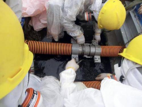Workers check joints on a pipe at a decontamination facility at the Fukushima nuclear power plant on October 9, 2013
