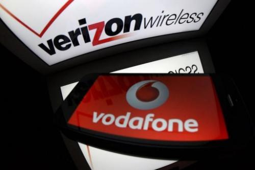 A picture taken on September 2, 2013 in Paris, shows the logo for Verizon Wireless and the logo of Vodafone