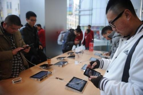 "A customer looks at an ""iPad mini"" at an Apple store in Shanghai on December 7, 2012"