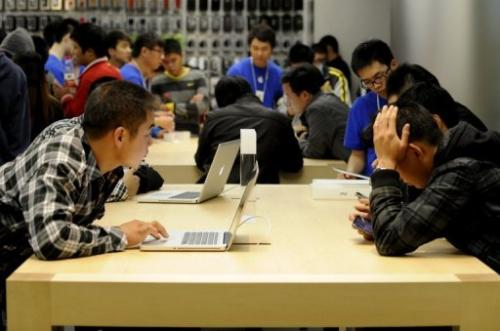 Customers look at Apple products in Apple's store at in Beijing on October 20, 2012