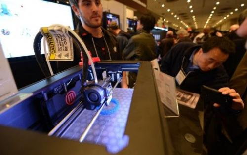"Visitors look at a 3D printer at the ""Inside 3D Printing"" event in New York on April 22, 2013"