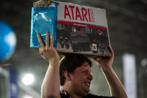 A man carries a box with an Atari game console as American Nolan Bushnell, founder of video game and home computer company Atari