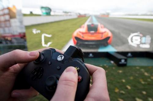 "A man plays the ""Forza 5"" driving game on a massive screen at a launch party for the new Microsoft Xbox One console in"