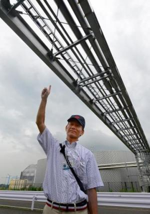 An engineer of Toyota Motor East Japan, car assembly subsidiary of Toyota Motor, points to pipelines that supply hot water to gr