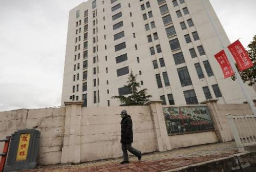 A person walks past a 12-storey building in Shanghai alleged in an Internet security firm Mandiant report in February 2013, to b