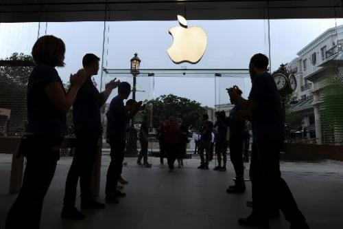 Apple employees applaud as they welcome the first shoppers arriving to purchase the new Apple iPhone 5S and 5C, at the Apple Sto