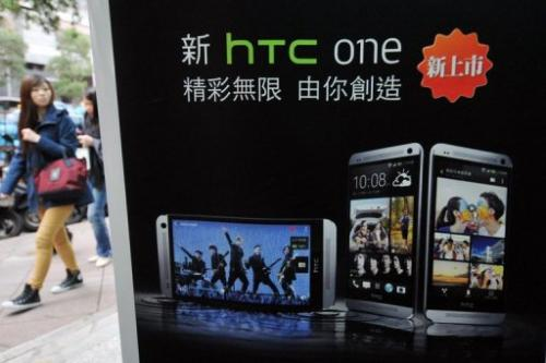 A woman walks past a HTC advertising in Taipei on May 2, 2013