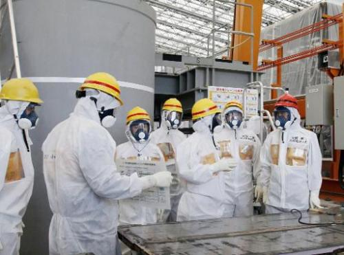 Japanese Prime Minister Shinzo Abe (right) is briefed by Fukushima Dai-ichi nuclear power plant chief Akiro Ono (third right) du