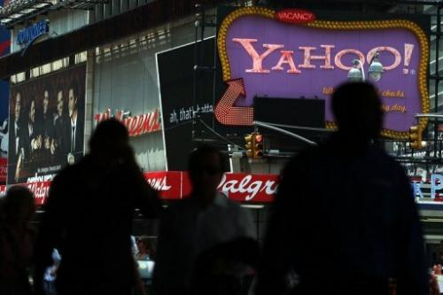 Pedestrians walk by a Yahoo! sign in Times Square on July 29, 2009 in New York City