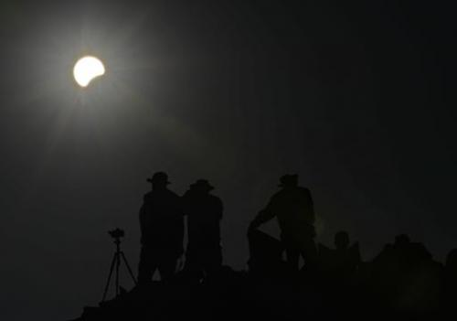 People watch as the moon appears to cover the sun on May 20, 2012 from the Pueblo Bonito ancient building at Chaco Culture Natio
