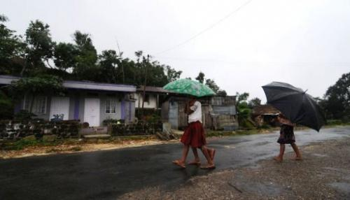 Children with umbrellaswalk through rain at Mawsawa village, northeast India on June 21, 2013