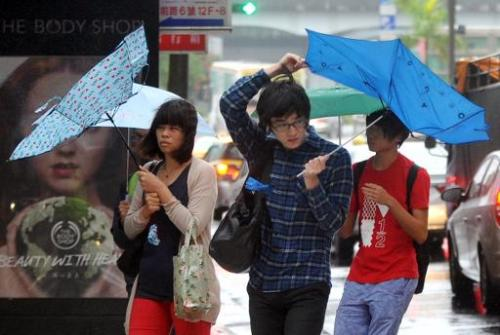 Pedestrians walk through strong winds and rain caused by Typhoon Fitow in Taipei on October 6, 2013