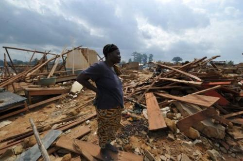 A woman looks at the ruins of Baleko-Niegre village in southwestern Ivory Coast, on June 22, 2013