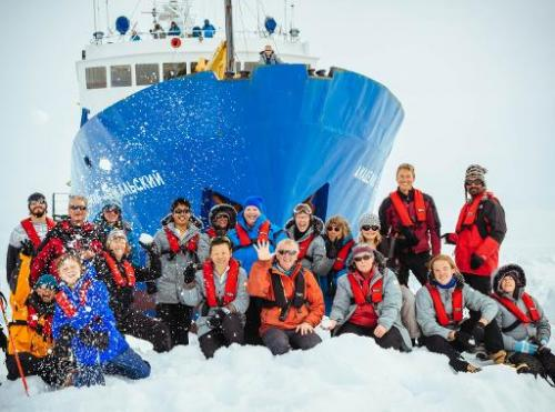 Image taken by Andrew Peacock on December 28, 2013 shows passengers posing for a photo with the MV Akademik Shokalskiy, which is