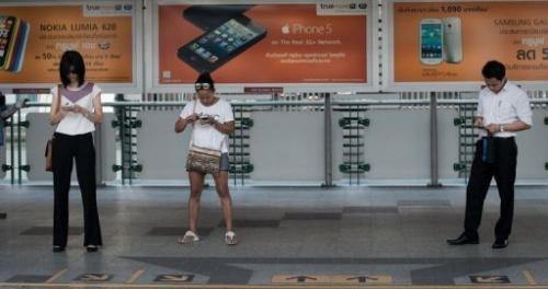 People look at their smartphones while waiting for a train at a BTS station in Bangkok, March 20, 2013