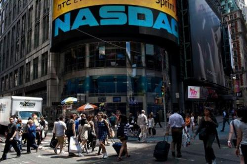 People walk past the Nasdaq exchange in Time Square on June 7, 2012 in New York City