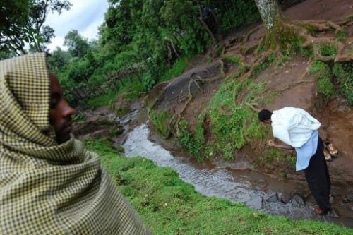 Members of the Ethiopian Orthodox church walk in the source of the Blue Nile in northern Ethiopia on August 17, 2010