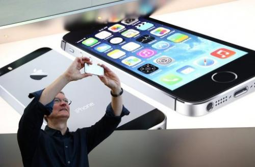 Apple CEO Tim Cook uses an iPhone to take a picture of customers waiting in front of an Apple store, September 20, 2013