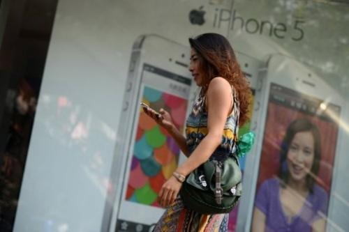 A woman looks at her mobile phone outside a store in Beijing on September 11, 2013