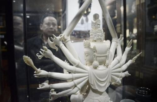 A Chinese man looks at an ivory Buddha carving at a shop in Beijing on February 20, 2013