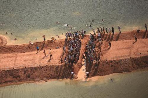Activists dig a gap through a temporary earthen dam over the Xingu River in Para, northern Brazil, on June 15, 2012 in protest a