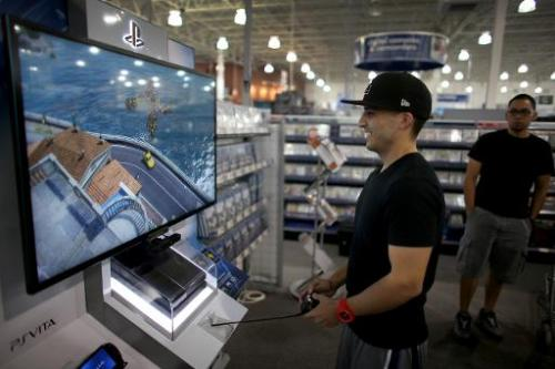 A customer tries out the new Sony PS4 at a Best Buy store after they went on sale at midnight on November 15, 2013 in Pembroke P