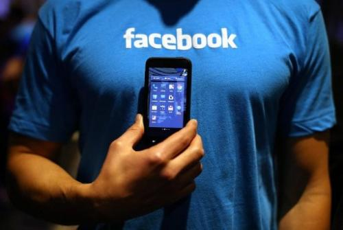 "A Facebook employee holds a phone that is running the new ""Home"" program on April 4, 2013 in Menlo Park"
