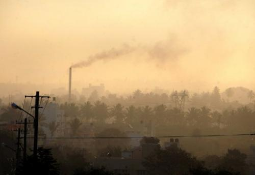 A factory chimney emits smoke as haze covers Bangalore, southern India on December 11, 2009
