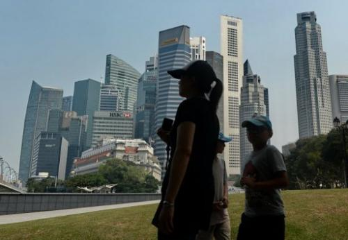 A family walks in the park near the financial district of Singapore on June 24, 2013